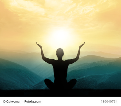 Yoga and meditation. Silhouette of man in mountains.